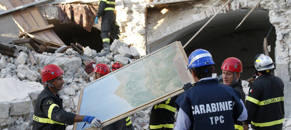 Firefighters recover paintings from a collapsed house in Amatrice, central Italy, Saturday, Aug. 27, 2016 where a 6.1 earthquake struck just after 3:30 a.m., Wednesday. Italians bid farewell Saturday to victims of the devastating earthquake that struck a mountainous region of central Italy this week. (AP Photo/Antonio Calanni)